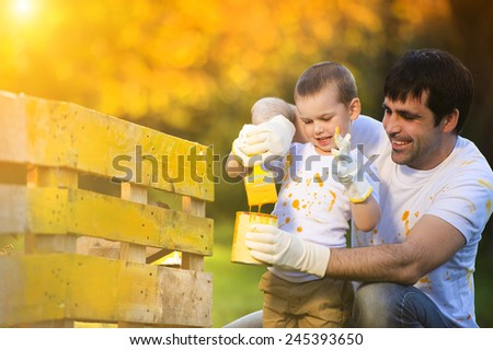 Cute little boy and his father painting wooden fence together on sunny day in nature - stock photo