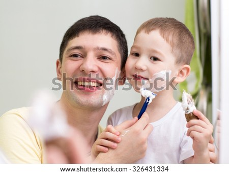 cute little boy and his father shave looking at mirror in bathroom - stock photo