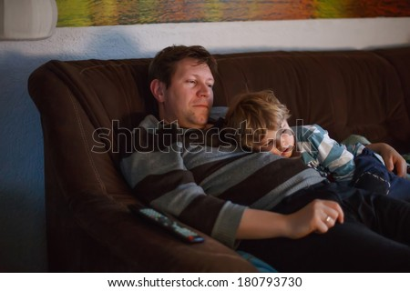 Cute little boy and his father watching tv, indoors in dark room at the evening - stock photo