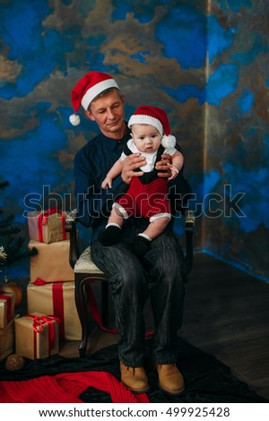 Cute little boy and his grandpa sitting at Christmas tree