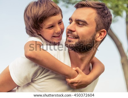 Cute little boy and his handsome young dad are looking at each other and smiling while resting in the park. Son is sitting pickaback - stock photo
