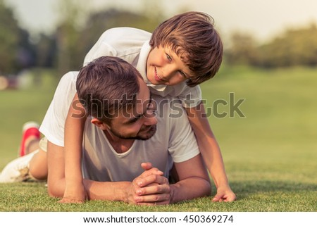 Cute little boy and his handsome young dad are smiling while lying on the grass in the park. Son is pickaback - stock photo