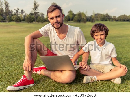 Cute little boy and his handsome young dad are using a laptop, looking at camera and smiling while sitting on the grass in the park - stock photo