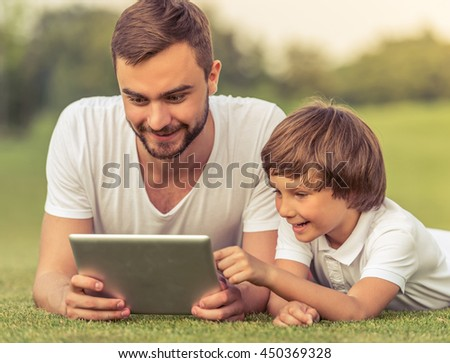 Cute little boy and his handsome young dad are using a tablet and smiling while lying on the grass in the park - stock photo