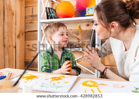 Cute little boy and his mother sitting and having fun with their painted hands in colorful paints