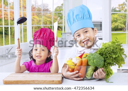 Cute little boy and his sister looking at camera while preparing healthy food in the kitchen