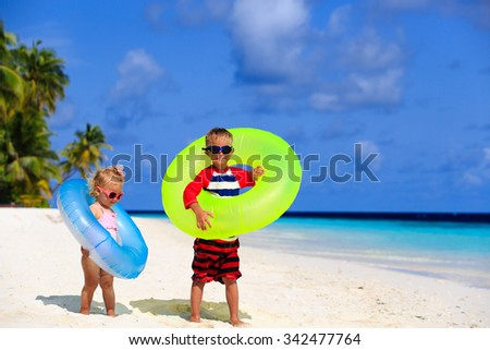cute little boy and toddler girl play on tropical beach - stock photo
