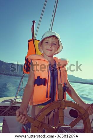 Cute little boy at sail boat wheel - stock photo