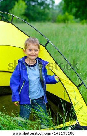 Cute little boy camping with tent outdoor. - stock photo