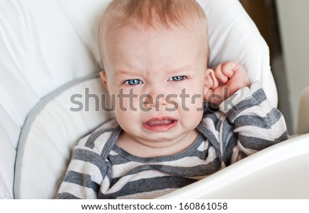 cute little boy crying and holding his ear on a white background - stock photo