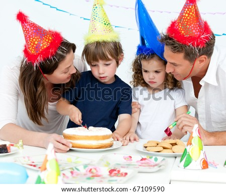 Cute little boy cutting a birthday cake for his family in the kitchen - stock photo