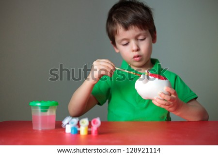Cute little boy diligently painting his piggy toy indoors - stock photo