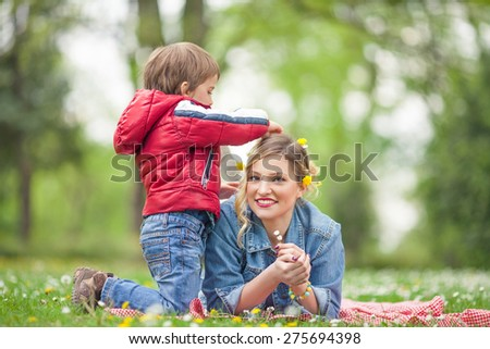 Cute little boy doing his mother's hair in a park - stock photo