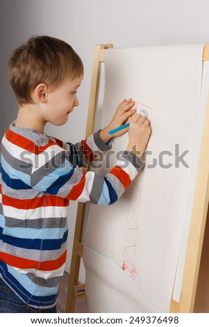 Cute little boy drawing a picture on easel