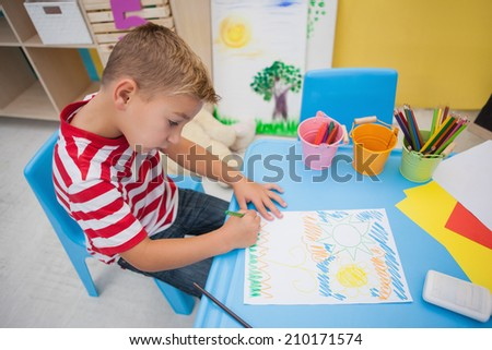 Cute little boy drawing at desk at the nursery school - stock photo