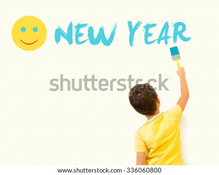Cute little boy drawing Happy new year 2016 with painting brush on wall background - stock photo