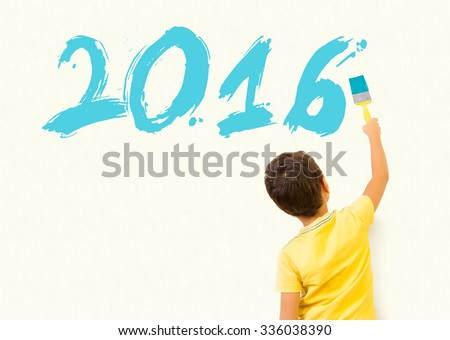 Cute little boy drawing new year 2016 with painting brush on wall background - stock photo