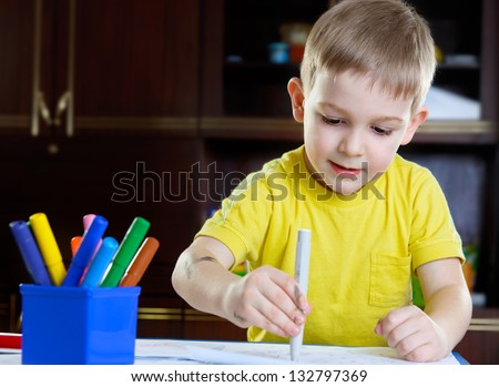 Cute little boy drawing with felt-tip pen at home