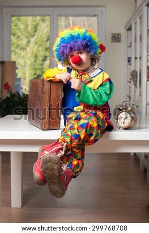 Cute little boy dressed as a clown with a suitcase and clock - stock photo