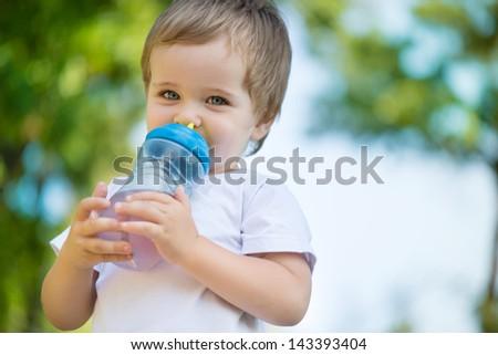 Cute little boy drinking water from feeding bottle - stock photo