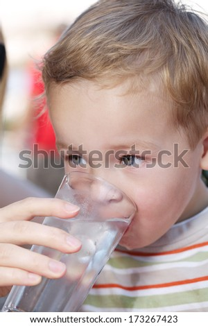 Cute little boy drinkng a glass of fresh water being held by his mother as he quenches his thirst