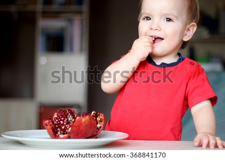 Cute little boy eating a red pomegranate, indoor close-up portrait, health nutrition concept - stock photo