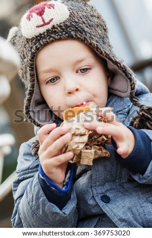 cute little boy eating cake outdoors in winter - stock photo