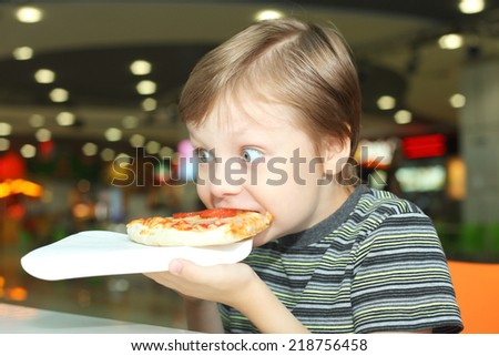cute little boy eating pizza - stock photo