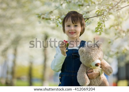 Cute little boy, eating strawberry in the park on a spring sunny afternoon, together with his big teddy bear - stock photo