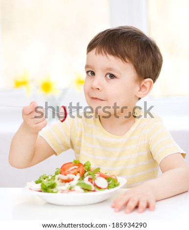 Cute little boy eats vegetable salad using fork - stock photo