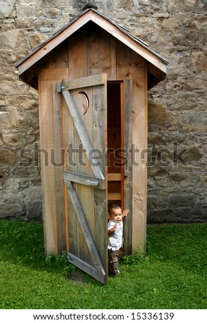Cute little boy emerging from old fashioned outhouse latrine