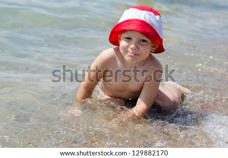 Cute little boy enjoying the sea splashing around in the shallows with a happy grin in his colourful sun hat - stock photo