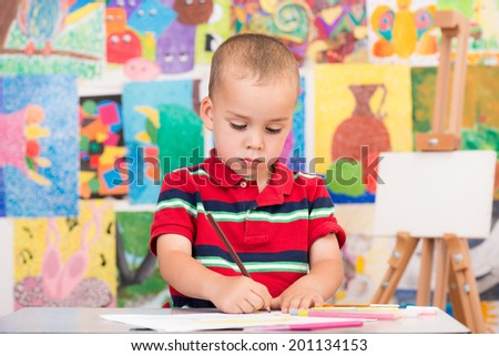Cute little boy enjoys drawing some interesting paintings.