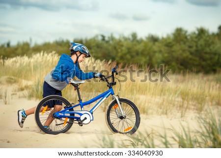 Cute little boy face on bike outdoors on autumn beach - stock photo