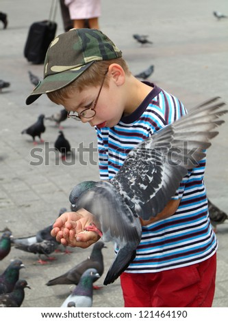 Cute little boy feeding pigeons in the city - stock photo