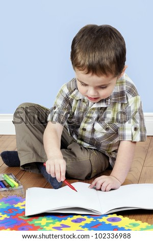 Cute little boy focused on coloring a blank white paper page with a red pen, preschool concept - stock photo