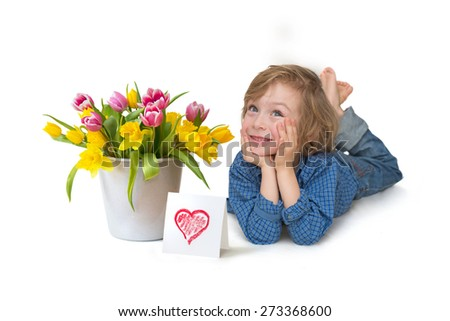 Cute little boy full length with a tulip bouquet and red heart card smiling lying on the floor isolated on white background   - stock photo