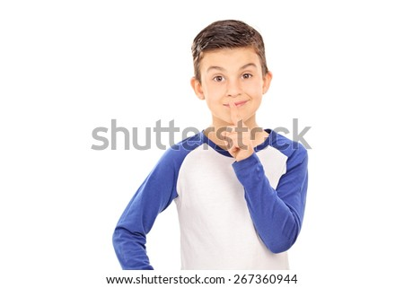 Cute little boy gesturing silence with his finger on his lips isolated on white background - stock photo