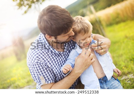 Cute little boy getting dressed by his father. - stock photo