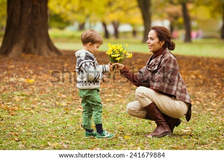 Cute little boy giving flowers to his mother - stock photo