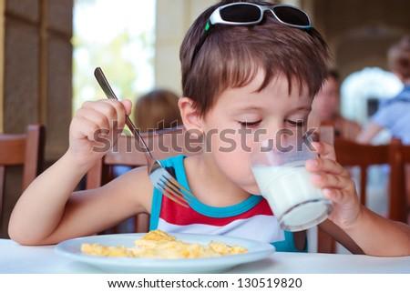 Cute little boy having delicious breakfast - stock photo