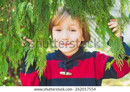 Cute little boy hiding behind the tree branches, having fun outdoors - stock photo