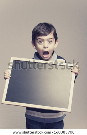 Cute little boy holding a blackboard - stock photo