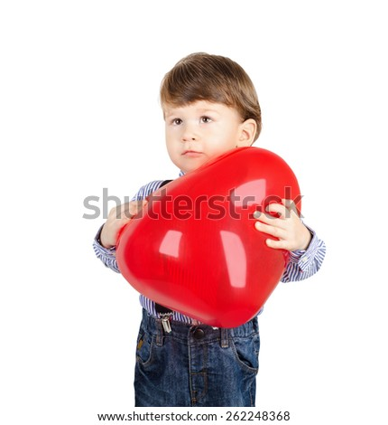Cute little boy holding a red heart shaped balloon isolated on white background