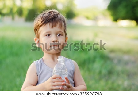 Cute little boy holding a water bottle in summer park - stock photo