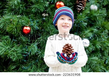 cute little boy holding huge tree cone at christmas time - stock photo