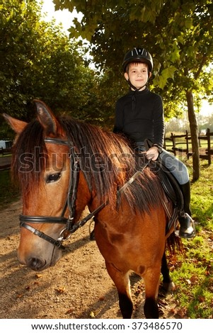 Cute little boy horseback riding in the green at autumn. - stock photo