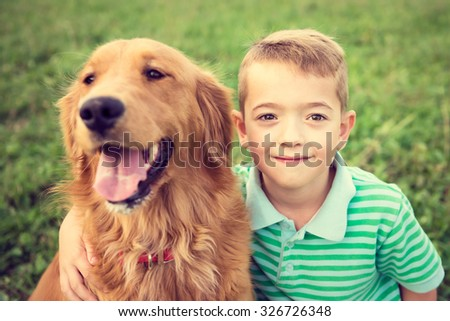 Cute little boy hugging his golden retriever pet dog - stock photo