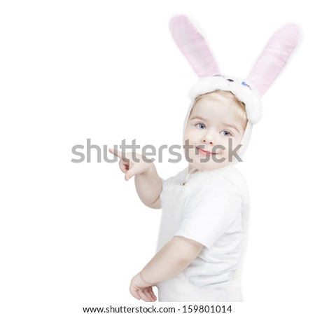 Cute little boy in a rabbit costume shows a finger to the side. White background. Studio shot - stock photo