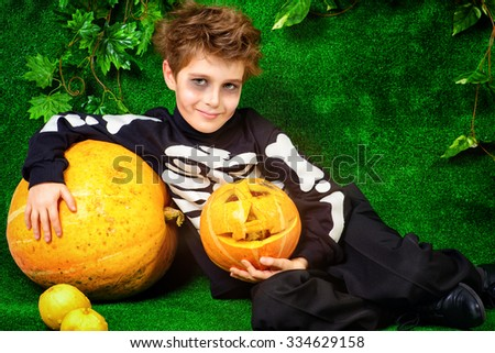 Cute little boy in a skeleton costume posing with pumpkins. Halloween.  - stock photo